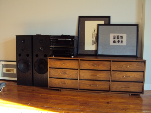"walnut chest holds ""vintage"" stereo equipment and woodblock prints"
